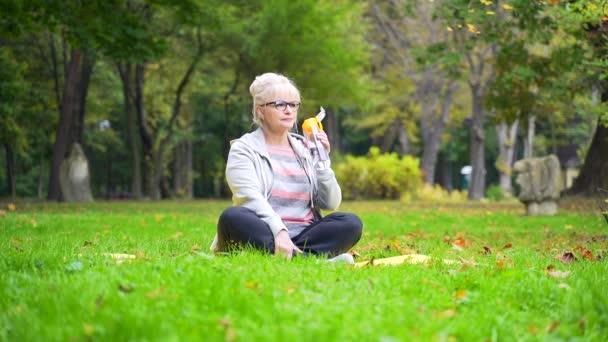 Moderne Seniorin auf dem Rasen, erschöpft nach dem Training, trinkt Wasser aus einer Flasche, die auf einer Yogamatte sitzt. Reifes Weibchen löscht Durst, genießt das Leben, ruht sich aus und erholt sich in der Natur im Park. Draußen