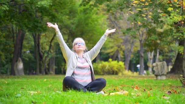 Portrét starší ženy v důchodu cvičení na podložce na trávníku park Stará žena dělá jóga praxe lotos pozici v přírodě. Aktivní zdravý životní styl v důchodu. Babička v brýlích a sportovním oblečení