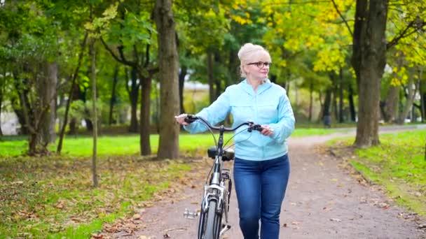 Šťastná starší žena v brýlích ležérní oblečení procházky v parku s kolem. stará cyklistka s retro motorkou se věnuje aktivnímu životnímu stylu v přírodě. Procházka podzimním lesem nebo městským parkem mimo