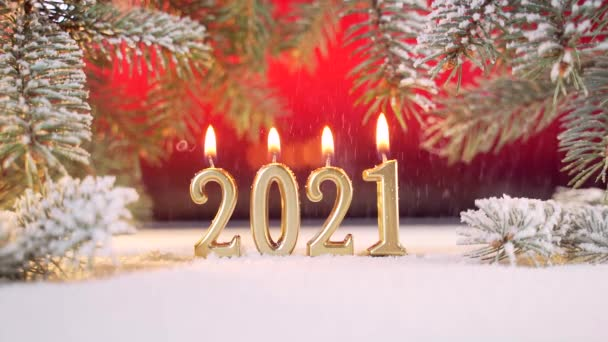 Közelről. Újévi arany gyertyák égnek 2021-ben. Havazik. Havazik. egy karácsonyfa ágain, vagy fenyő egy vörös háttér. Makró. Helyezze be a szöveget. Fénymásolási hely