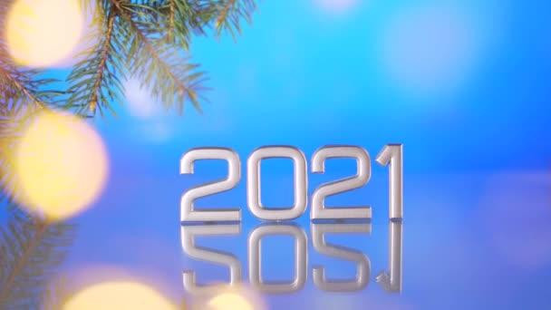 közeli dátum 2021 kék háttér, elmosódott bokeh a koszorúk és a fény. Egy fenyőágról. Új év 2021 díszítő üveg felületen