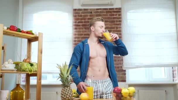 Atletický muž pije ovocný džus ze sklenice doma v kuchyni. Atraktivní sexy fitness chlap na smoothie, koktejl nebo vitamin zdravý nápoj nebo čerstvé