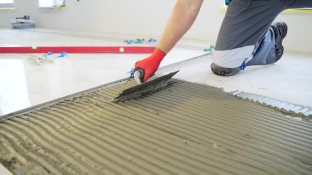 Stavební opravy pokládání keramických dlaždic na betonovou podlahu pomocí nástrojů a lepidel. Zblízka ruka stavitele mistra, zářezy lopatka uvedení dlaždice lepidlo mix s zářezem lopatky