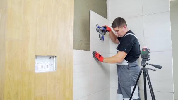 Muž pracovník profesionální mistr kladení keramických dlaždic na stěnu v koupelně. Portrét zkušený opravář umístění velkých dlaždic. stavitel instalující dlaždice při opravách renovace