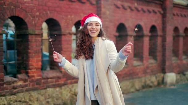 portrét šťastné mladé ženy v kabátě a Santa Claus vánoční klobouk s jiskry v rukou na ulici. Šťastná dívka se usměje a podívá se do kamery. Koncept nového roku, zimní prázdniny, sněžení