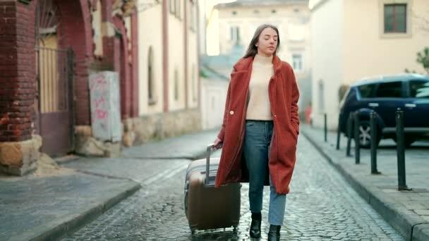 Nahaufnahme Porträt einer jungen attraktiven Touristin mit einem Koffer, die allein die Straße der Altstadt hinunterläuft und sich umsieht. Geschäftsreisende im Mantel besucht Stadt im Winter Herbst kalten Frühling