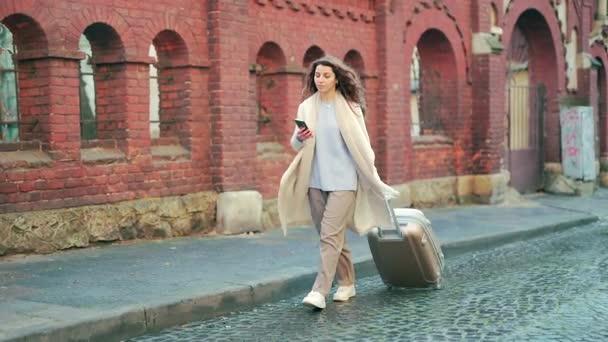 Porträt einer jungen Touristin mit einem Koffer auf Rädern, die mit einem Handy in der Hand allein durch die Altstadt läuft und sich umsieht. Geschäftsreisende Frau im Mantel genießt die Bewerbung