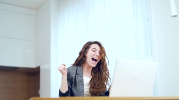 Euphoric lady gets new distance job opportunity, reads good news in email, rejoices victory, feels motivated. Excited young woman winner looks at laptop celebrates online success sits at table a home