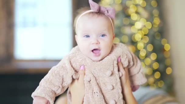 Close up Portrét Roztomilý 6 měsíců staré dítě vypadá a drží fotoaparát. Dětský obličej s mašlí na hlavě a pleteným svetrem v pohybech mámy. pozadí vánočního stromečku rozmazané bokeh
