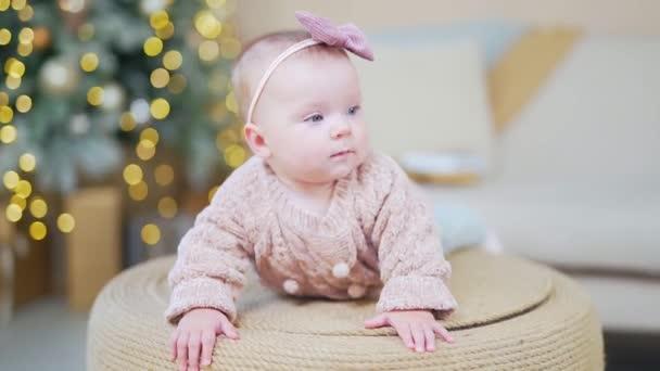 Close Up Portrét 6 měsíců stará Baby Girl drží hlavu ležící na břiše, dívá se na kameru. Novorozené dítě v útulné pletené oblečení a s lukem na hlavě pozadí rozmazané Bokeh vánoční strom