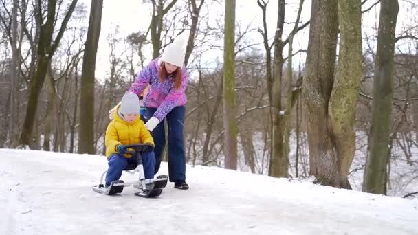 Die junge Mutter geht mit einem kleinen Kind im Park im Schnee spazieren. Glückliche Mutter beim Rodeln mit ihrem Sohn. Zeit miteinander verbringen. Freizeit mit Kindern draußen in der kalten Jahreszeit. Draußen