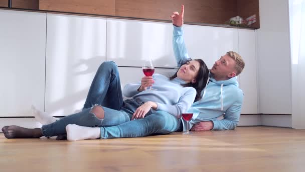 young happy married couple man and woman sitting on the floor and celebrating moving to a new apartment or home. They drink wine and plan the interior near the cardboard boxes. dream of modern design