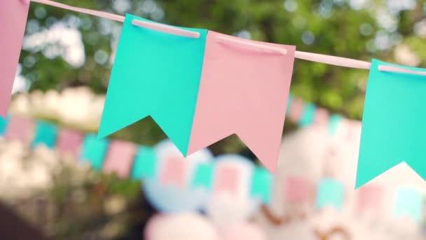 Díszítés a születésnapi ünnepség előtt. Pasztell zászlók lógnak a fák között. Nyári kerti parti. Szabadtéren, esküvőn. Nyár közepe, festa junina koncepció. Természetes homályos háttér, napos köd.