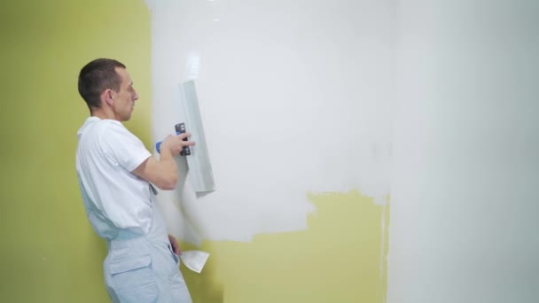 experienced repairman is plastering wall, using spatula, putty knife and white modern mortar, stuccoing. Portrait professional man putty plaster. skilled craftsman, specialist makes white surface