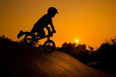 Silhouette Of Stunt Bmx Child Rider - color tone tuned