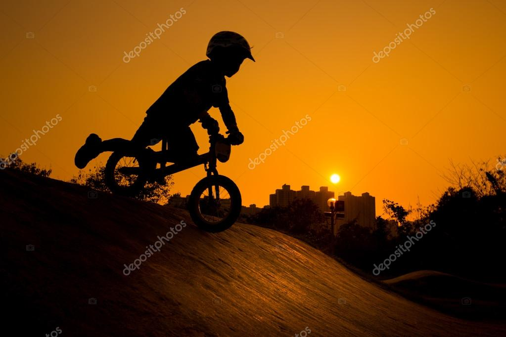Silhouette Of Stunt Bmx Child Rider - color tone tuned