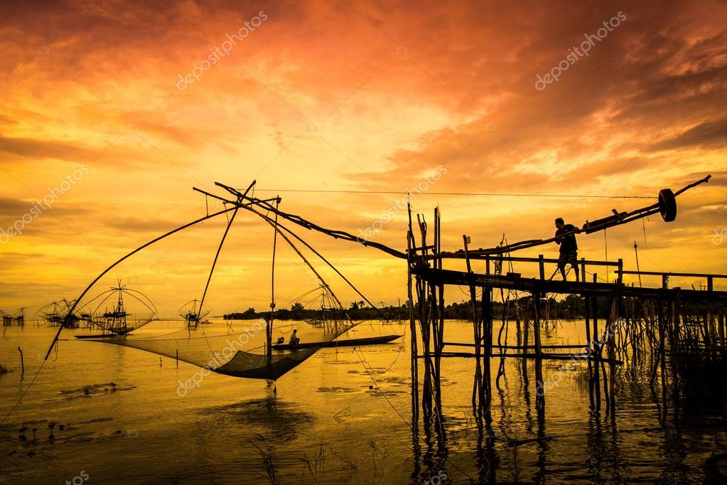 Fisherman and traditional fishing equipment in water at sunset