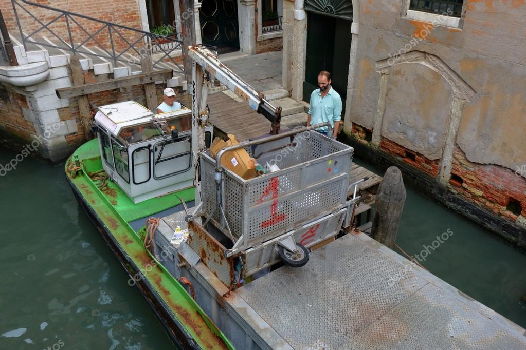 Venice. Boat with hydraulic arm and tank for garbage collection