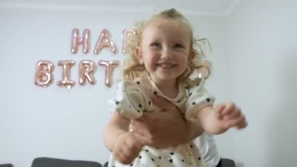 glückliches kleines Mädchen genießt ihre Kindheit beim Spielen mit Papa an ihrem Geburtstag