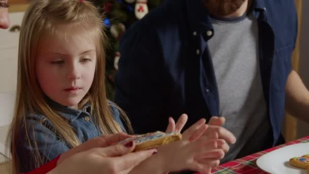the daughter demonstrates her work to her parents and gives her mother a taste of gingerbread
