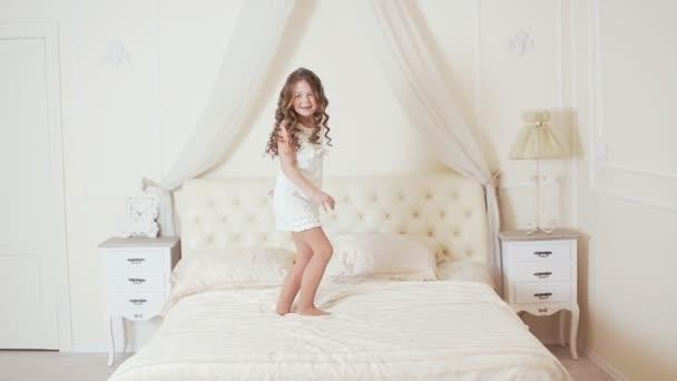 glückliche Mädchen springen und tanzen auf dem Bett