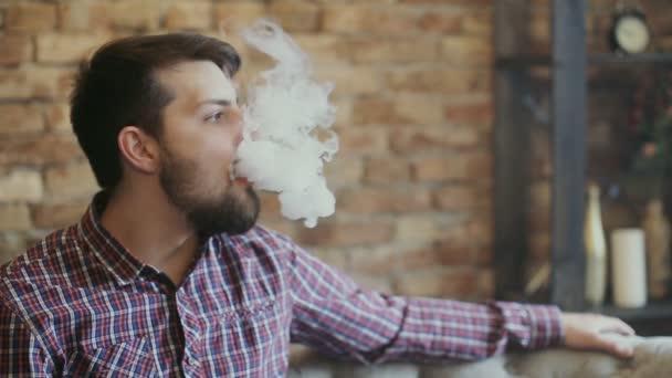 Muž Exhaling kouř z výparníku. Zpomalený pohyb