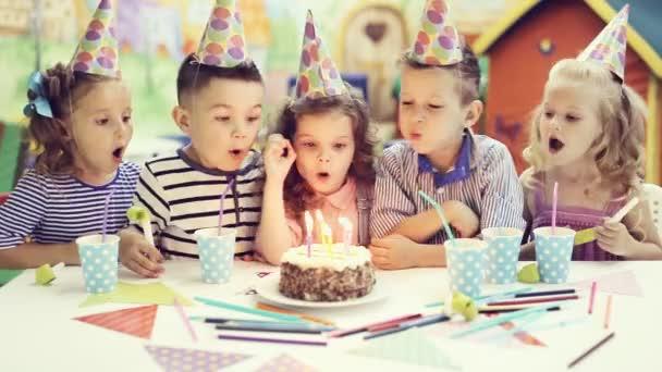 děti foukání svíčky na narozeninový dort
