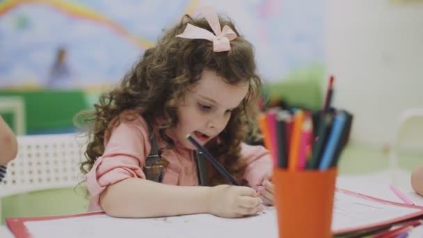 dívka, kresba na papíře v herně s tužky