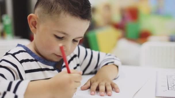 malý chlapec kreslení pastelkami na papír