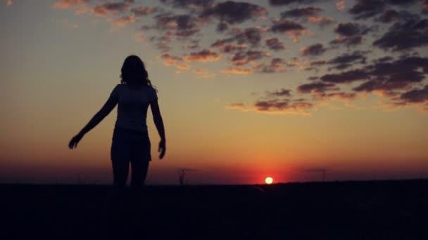 donna che fila su priorità bassa di tramonto