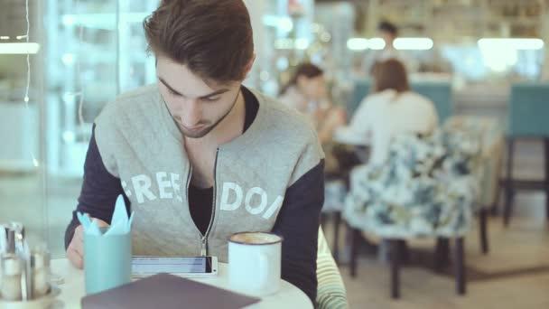 Fiatal ember ül a café tabletta számítógép