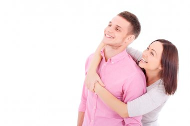 A young couple standing together, hugging and looking at somethi