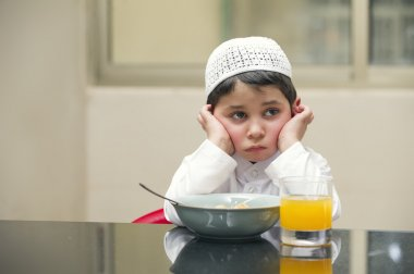 Arabian kid having breakfast of cornflakes and orange juice
