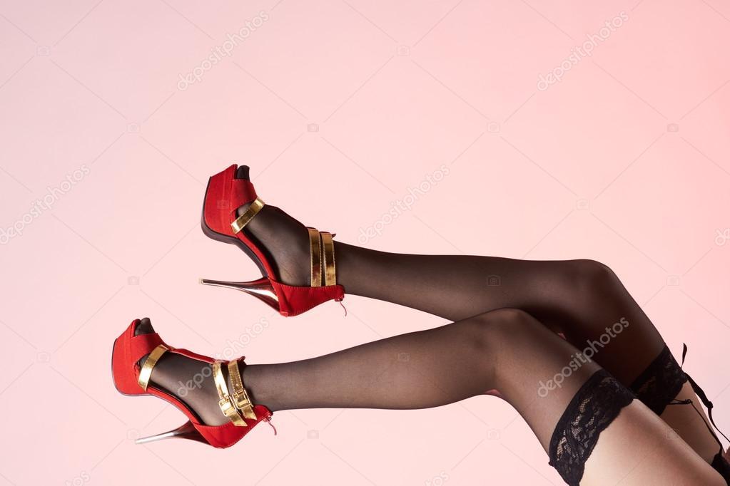 1bca1eb3b3 Piernas sexy de mujer con plataforma y tacones de oro zapatos rojos en  medias de nylon