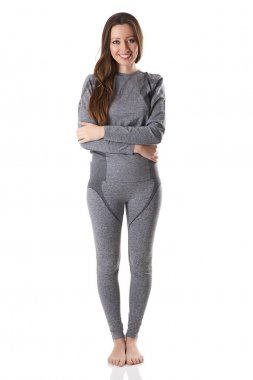Beautiful woman staying hugging herself with her arms in gray sports thermal underwear.