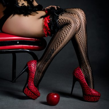 Beautiful legs in red high heels with a red apple