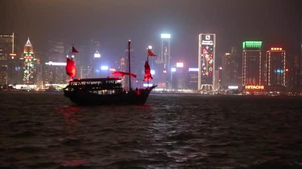 Híres Red Junk vitorlás halad előtt szép Hong Kong városkép éjjel
