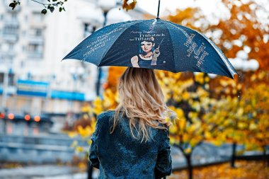 Blonde girl with umbrella on street