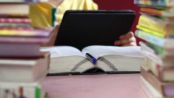 selektivní zaměření na knihu a pero, zatímco dítě používá tablet v pozadí