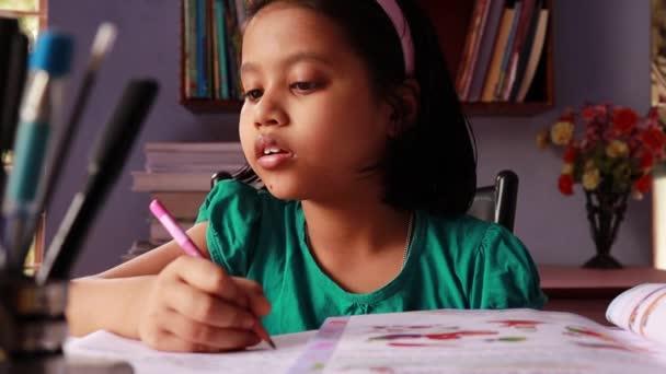 Ein süßes indisches Mädchen ist beim Lernen zu Hause verwirrt