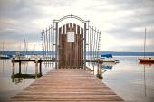 Fotografie Der Steg zu den Booten ist durch ein Holztor und Metallstangen am Ammersee versperrt.