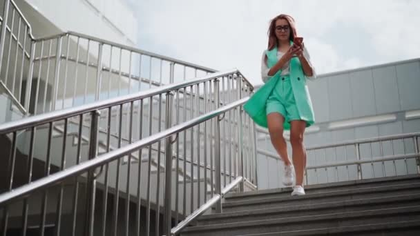 Eine schöne, glückliche Frau mit Brille und modischer Kleidung in türkisfarbener Farbe mit einem Handy in der Hand geht die Treppe hinunter, lächelt und lacht vor Freude über den Erfolg. Zeitlupe.