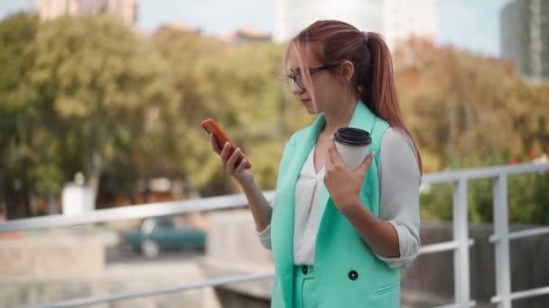 Schöne Geschäftsfrau mit Brille und modischem türkisfarbenem Sakko per Handy-SMS auf der Straße. Erfolgreiche Dame neben Firmenbüro tippt SMS auf Smartphone. Zeitlupe.