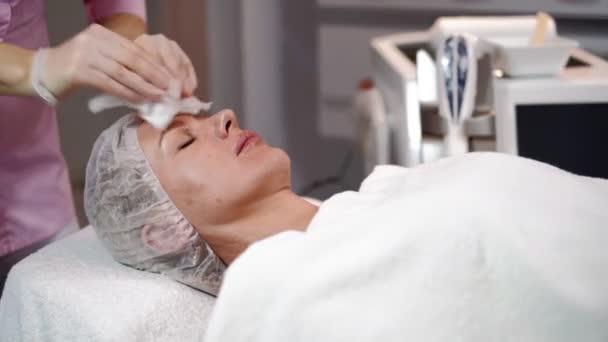 Žena kosmetička se připravuje na laserové omlazení a odstranění ochlupení obličeje ženy ležící na lékařské pohovce v salonu krásy. Kosmitologie, epilace a lázeňský koncept. Péče o tělo a kůži. Detailní záběr