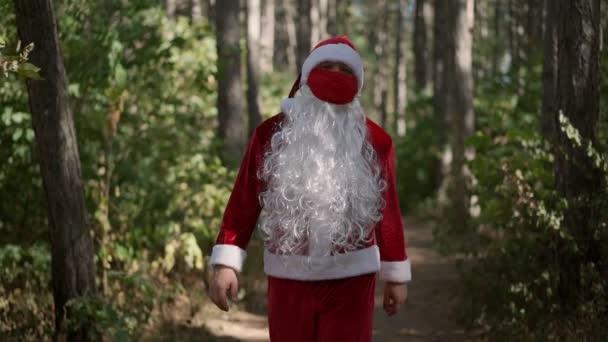 Chlápek v obleku Santa Clause s červenou ochrannou lékařskou maskou na obličeji kráčí sám lesem. Koronavirus a Vánoce. Nový rok během karantény a covid-19. Zpomalený pohyb