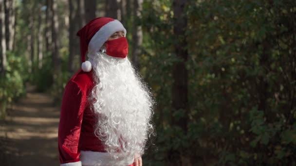 Smutný chlapík v obleku Santa Clause s červenou ochrannou lékařskou maskou na obličeji stojí sám v lese. Koronavirus a Vánoce. Nový rok během karantény. Zpomalený pohyb