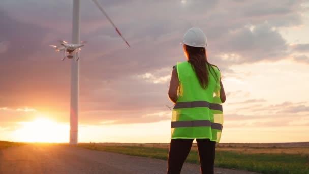 Frau Ökologie Spezialistin in Uniform und Helm hält Steuerknüppel Steuerung fliegenden Drohne arbeitet an Windmühle auf schönen Sonnenuntergang Hintergrund. Moderne Technik. Zeitlupe.