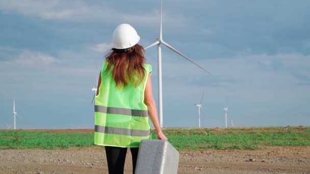 Woman Professional Ecology Engineer in uniform and helmet with special equipment in hand goes to service a windmill on beautiful sky and field background. Alternative energy concept. Slow motion.