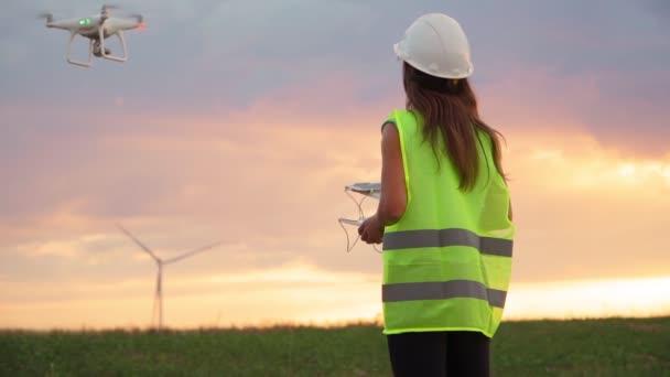 Ökologie-Ingenieurin in Uniform und Helm mit Steuerknüppel steuert fliegende Drohnen bei der Arbeit an einer Windmühle vor wunderschönem Sonnenuntergang. Alternative zu elektrischer Energie. Zeitlupe.