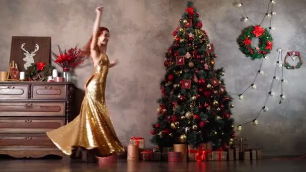 Krásná žena ve zlatých večerních šatech točí a tančí v blízkosti vánočního stromečku